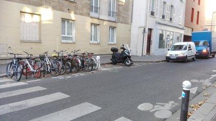 Photo d'un parking vélo devant un passage piéton.